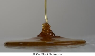 Close-up of honey dripping. Pouring honey on surface. Slow Motion.