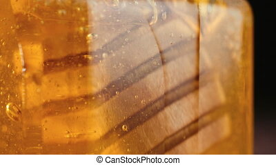 Close up of honey stick in jar