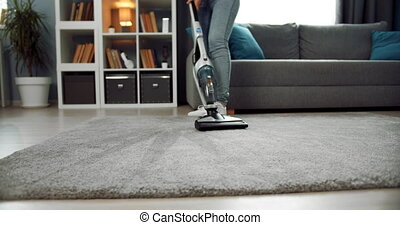 Close up of housewife cleaning carpet with modern vacuum - ...