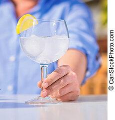 close-up of human hand holding fresh lemonade