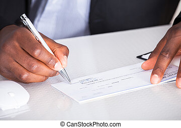 Human Hand Writing On Cheque - Close-up Of Human Hand...