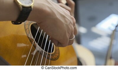 Close-up of human hands playing classical guitar