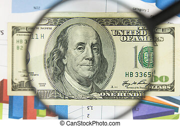 Close-up of hundred dollars through a magnifying glass. Business background. Money research concept.