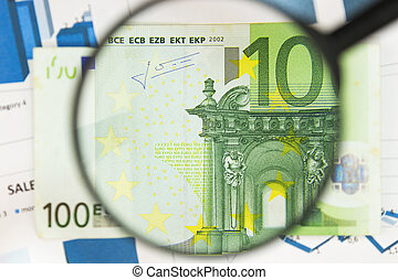 Close-up of hundred euros through a magnifying glass. Business background. Money research concept.