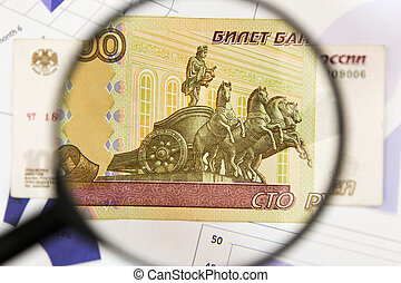 Close-up of hundred rubles through a magnifying glass. Business background. Money research concept.