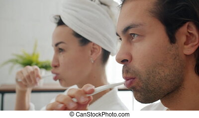 Close-up of husband and wife brushing teeth in bathroom caring for dental health