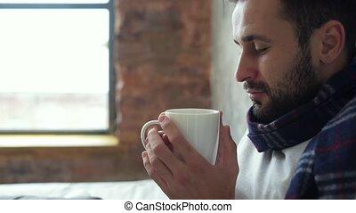 Close up of ill man enjoying cup of tea - Gaining strength....