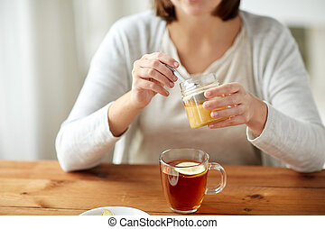 close up of ill woman drinking tea with honey