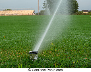 Close up of in-ground sprinkler system spraying local sports playing field