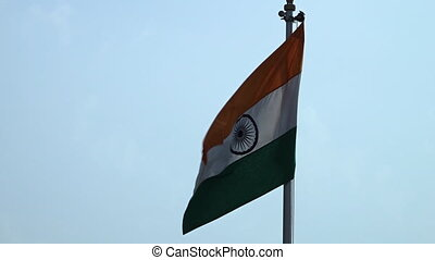 Close up of the Indian flag, raised up on a pole, flapping in the wind against a blue sky