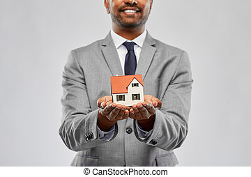 close up of indian man realtor with house model - real ...