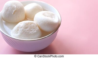 close up of indian sweet in a white bowl on pink background