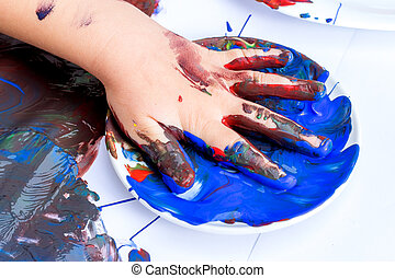 Close up of infant hand soaked in blue paint.