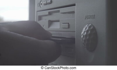 "Close-up of inserting and removing an old-style 5.25"" floppy..."