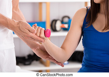 Close-up Of Instructor Assisting Woman While Doing Exercise