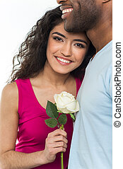 Close up of interracial couple holding white rose. African American man and indian woman looking into camera