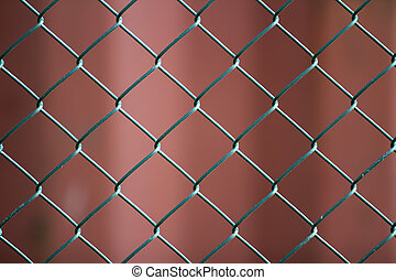 Close-up of isolated painted simple geometric black iron metal wire chain link fence eon dark red background. Fence, protection and enclosure concept.