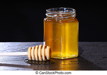 Close-up of jar of honey and wooden stick