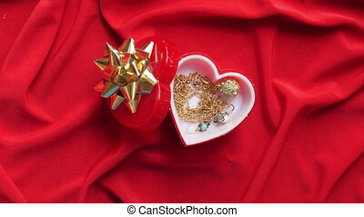 Close up of jewelry in heart shaped box on red satin