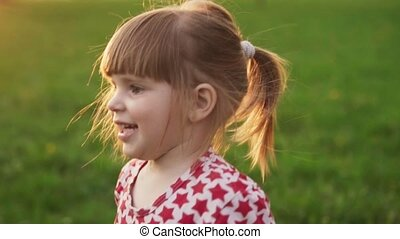 Close-up of joyful little girl at sunny summer day in park