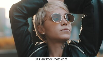 Close up of joyful young woman with bright hair and sunglasses standing with hands over the head. People and style concept. High quality 4k footage