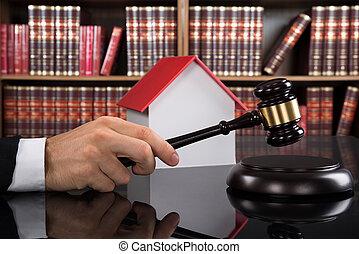 Judge With House Model Hitting Gavel