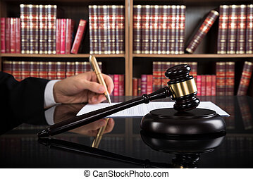 Close-up Of Judge Writing On Paper And Gavel At Desk