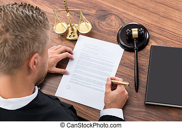 Close-up Of Judge Writing On Paper In Courtroom