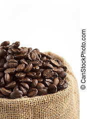 close up of jute bag with coffee beans on white background
