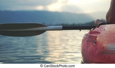 Close up of kayaker sits in kayak and looks amazing sunset. slow motion.