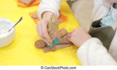 Close up of kid decorating the gingerbread cookies