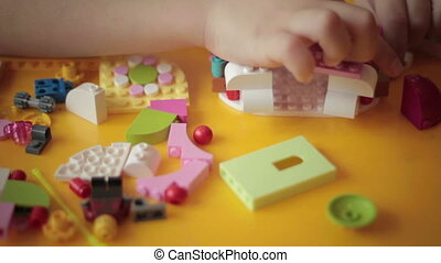 close up of kid hand moving lego construction 7