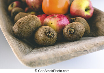 Close Up of Kiwis, Apples, and Oranges in Wooden Tray