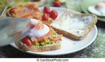 Close up of knife cutting toast with pouched egg, avocado and salmon