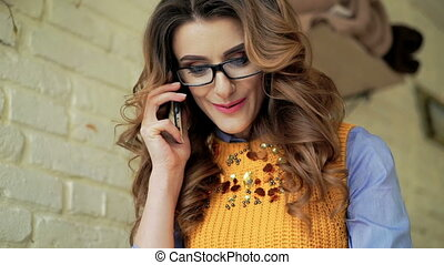 Close up of lady's face speaking on the phone, writing ang smiling