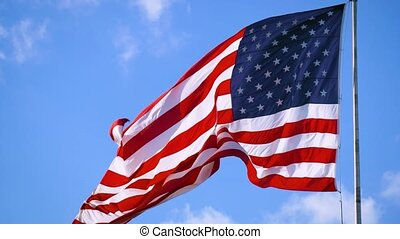 American Flag Waving Under A Blue Sky With Clouds - Close up...