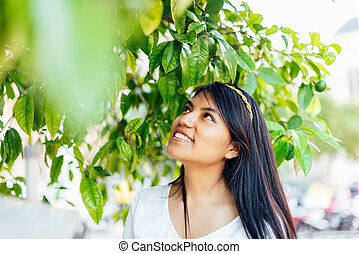 close-up of latin woman dressed in white among branches of orange tree looking up