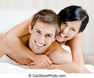 Close up of laughing couple who plays in bed-room