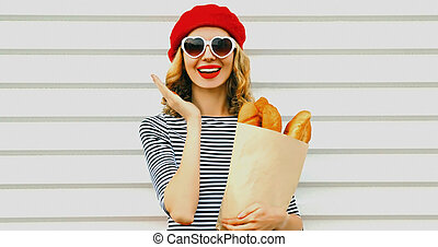 Close up of laughing young woman wearing a french red beret holding paper bag with long white bread baguette over a white background