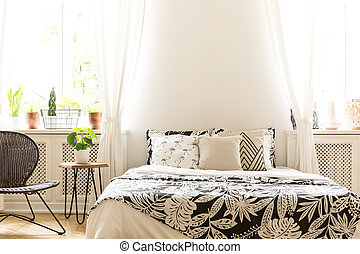 Close-up of leaf pattern black and white covers on a bed in a sunny bedroom interior. A rattan and metal chair and a stool with a plant in the room. Real photo.