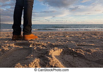 Close-up of legs - Girl looking the sea on the beach at sunset - winter season - story telling sequence