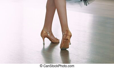 Close-up of legs of a girl in ballroom dances. Slow motion