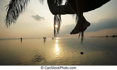 Close up of legs of a tourist sitting on a palm tree during...