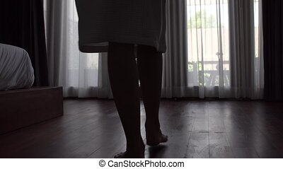 Close-up of legs of woman in bathrobe unveil curtain, standing near the window in home.