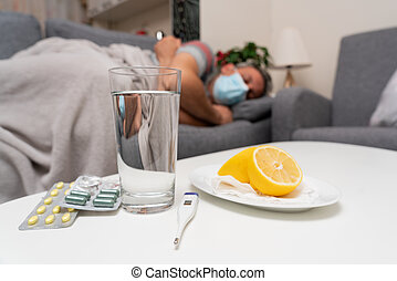 Close-up of lemon and cold flu covid19 treatment medicine on table near bad selective focus man wearing surgical disposable mask sleeping in background as immunity during pandemic concept