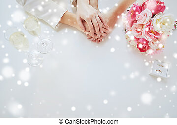 close up of lesbian couple hands and wedding rings