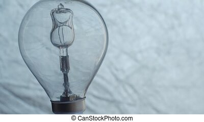 Close Up of light bulb over silver background. Electricity.