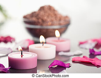 Close up of lighted candles with a brown gravel bowl and petals