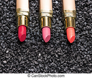 Close-up of lipstick on anthracite surface with copy space