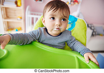 Close up of little boy sitting on the high chair
